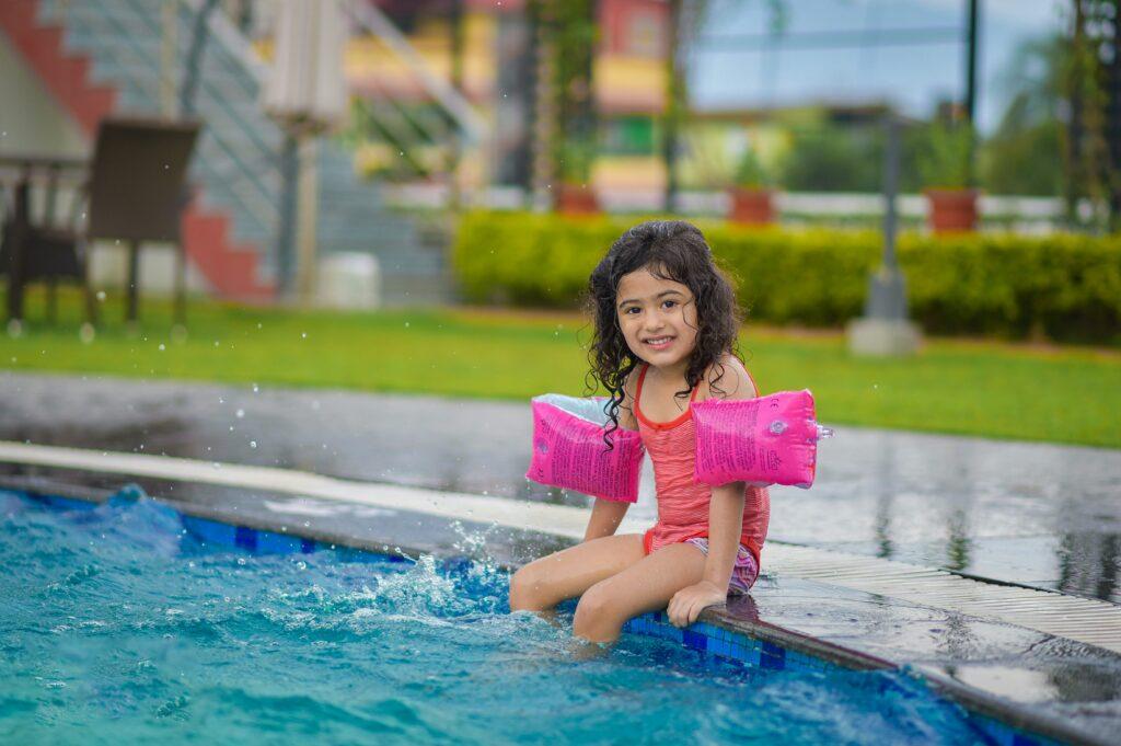 Image d'une enfant au bord d'une piscine